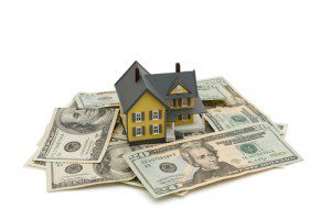 A small model of a house is sitting on topi of a pile of cash showing some sort of home costs or real estate value
