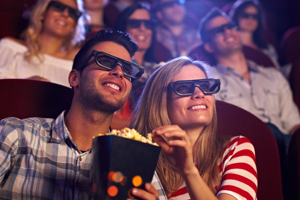 Couple eating popcorn with 3d glasses on in a las vegas movie theater