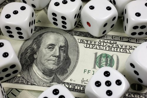 Picture of dice on top of 100 dollar bill indicating a gamble