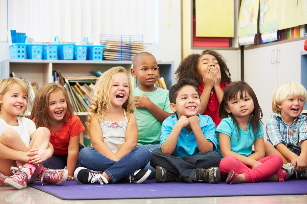Children are sitting on a mat laughing and could be a school in Anthem, NV