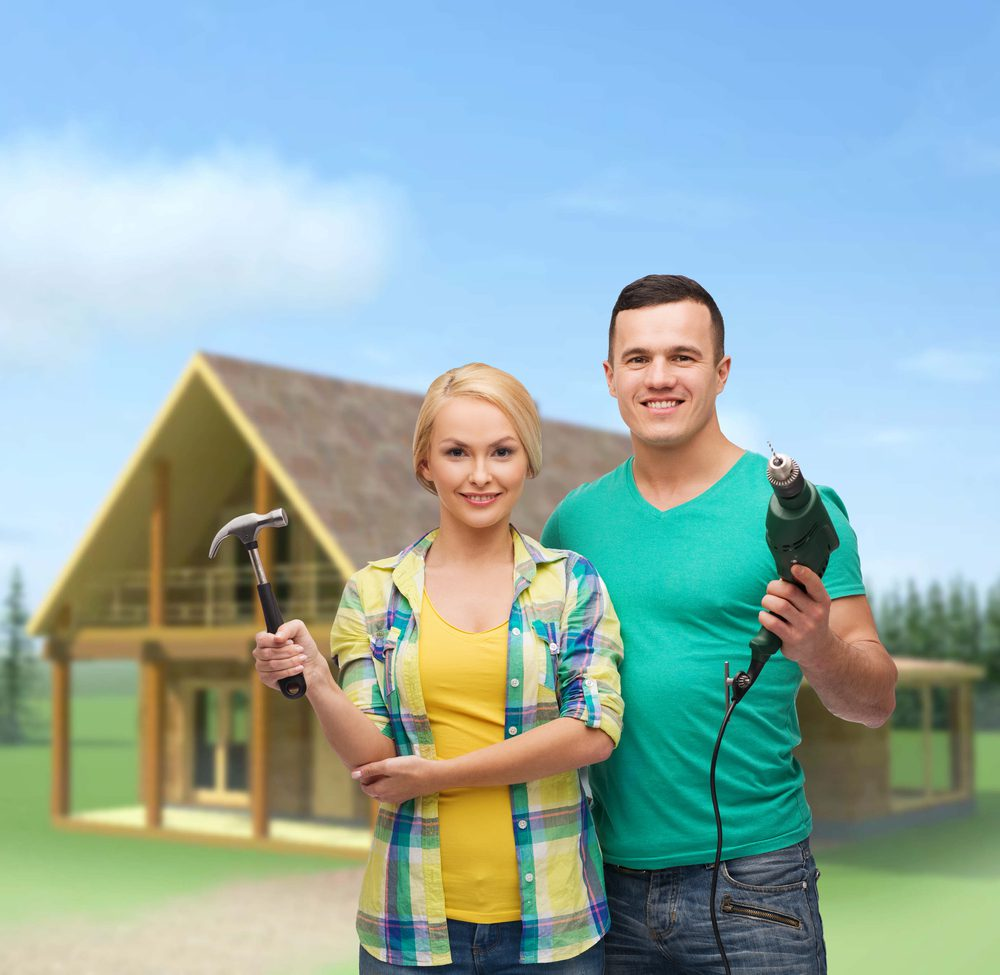 Young couple stands in front of house with a hammer and drill gun as they begin to fix up a home for flipping