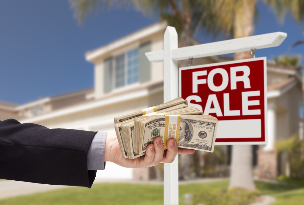 A hand is holding a lot of cash offering it to a home seller in front of a for sale sign