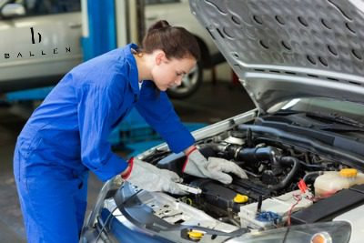 woman mechanic working under hood of car