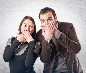 Couple has hands over their mouth so that they don't say the wrong things to a home buyer while selling their house