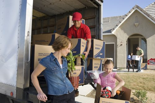 Family looks happy as they are moving into new home. Truck is shown with boxes and mover helping.