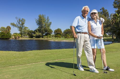 Man and Woman are at the golf course in Sun City. Each holds a club.