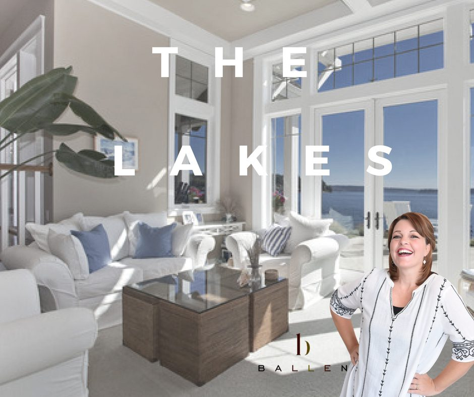 Interior of home with floor to ceiling windows showing blue skies, lori ballen is on picture with the words The Lakes