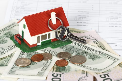House with a money including hundred dollar bills and change to show closing costs
