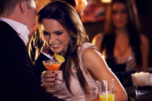 Girl holds an orange cocktail as she leans in to hear a man speak. Clearly at a bar.