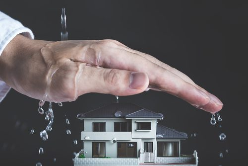 Hand is held over house as it rains. Hand appears to be attempting to protect the house