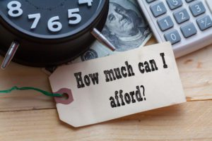 money, calculator are on the table with a tag that reads how much can i afford