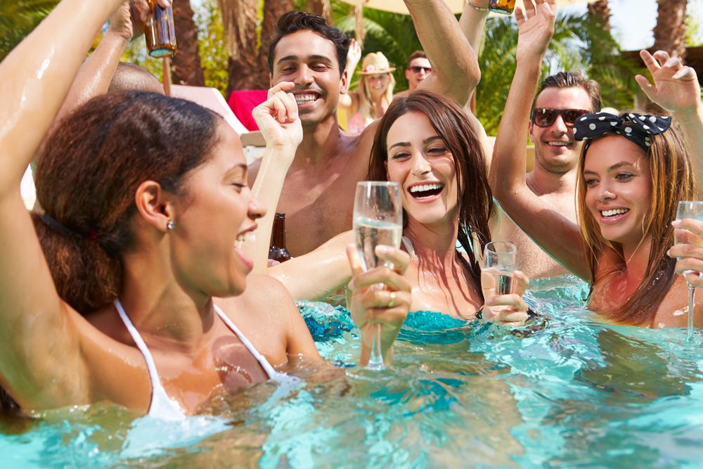 People are in the pool having a good time drinking champagne