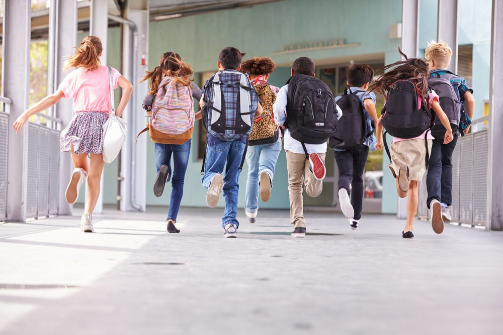 Back to School, Middle school or elementary school kids are running into school with back packs