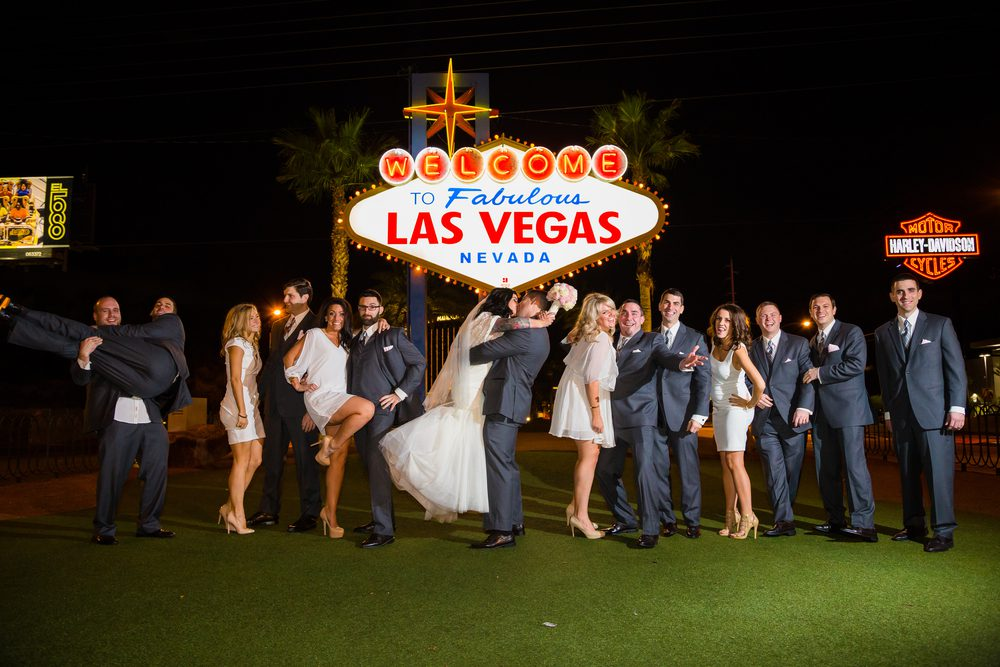 Wedding Party standing inside of the Welcome to Las Vegas sign