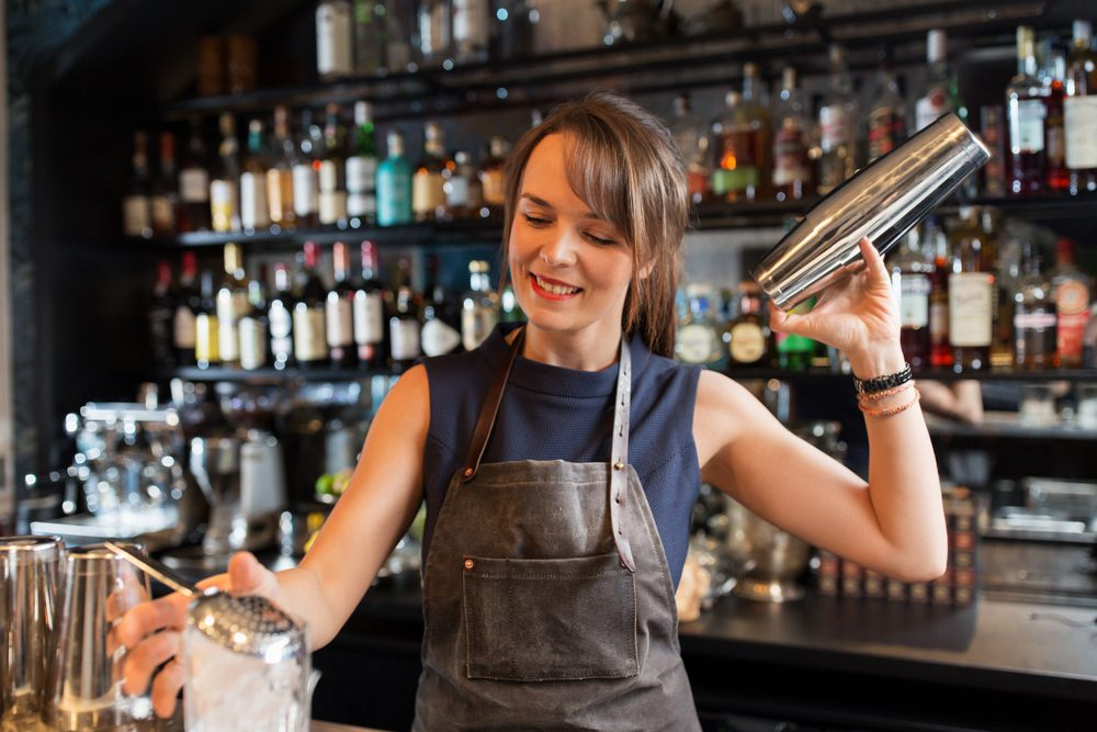 Young female is mixing drinks at a bar and is smiling