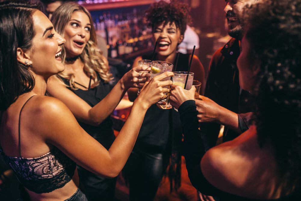 Group of people in a nightclub with drinks doing a toast