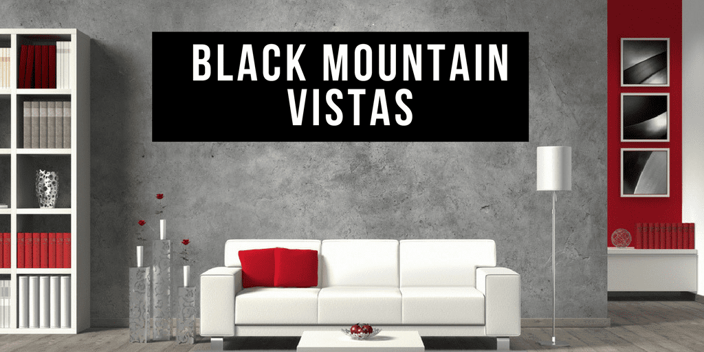 Staged Living Room with White couch, Red pillow, walls says black mountain vistas