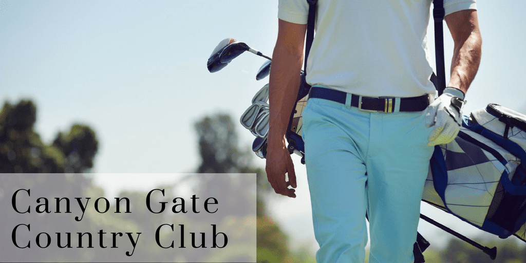 Man in blue pants walks on golf course holding gold club in bag on his back - sign reads Canyon Gate Golf Club