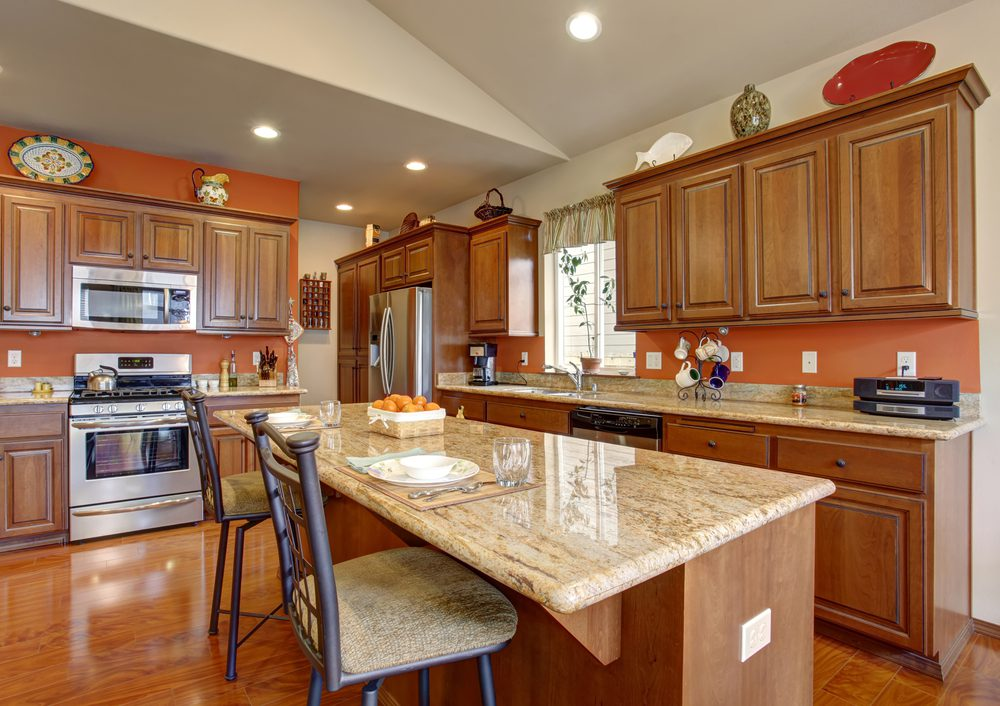 Kitchen that could be in Coronado Ranch features large island, bar stools, oak cabinets