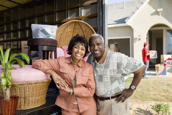 Senior couple looks very happy standing in front of a moving truck in front of a house they just bought