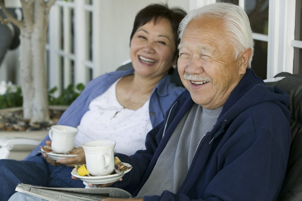 Senior Couple is at home in Solera at Anthem drinking tea and laughing on the porch