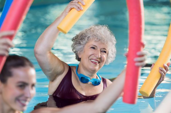 A woman does water aerobics at the 55+ senior community swimming pool