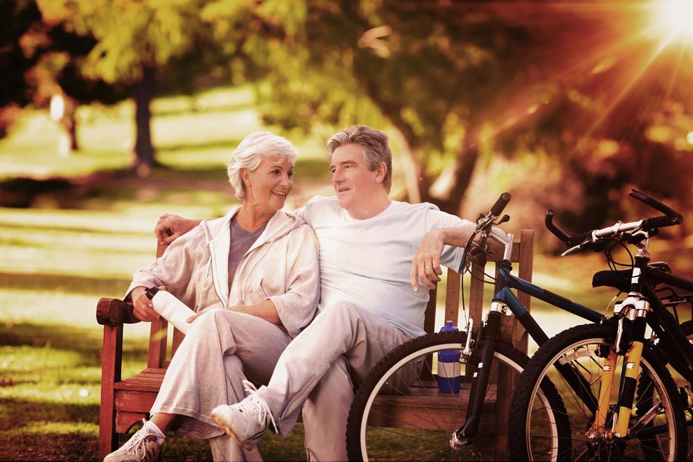 Seniors at a Park near Cadence neighborhood in Henderson with bicycles and trees behind them as they sit on a bench in the sun