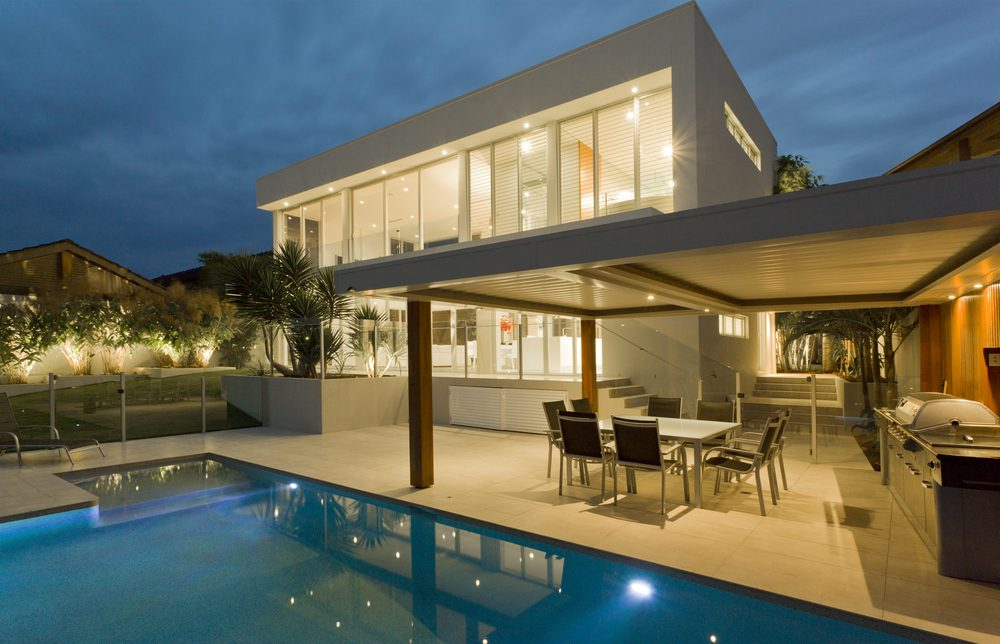 Back of mansion with covered patio, chairs and table, pool, night shot with lights on, home is white