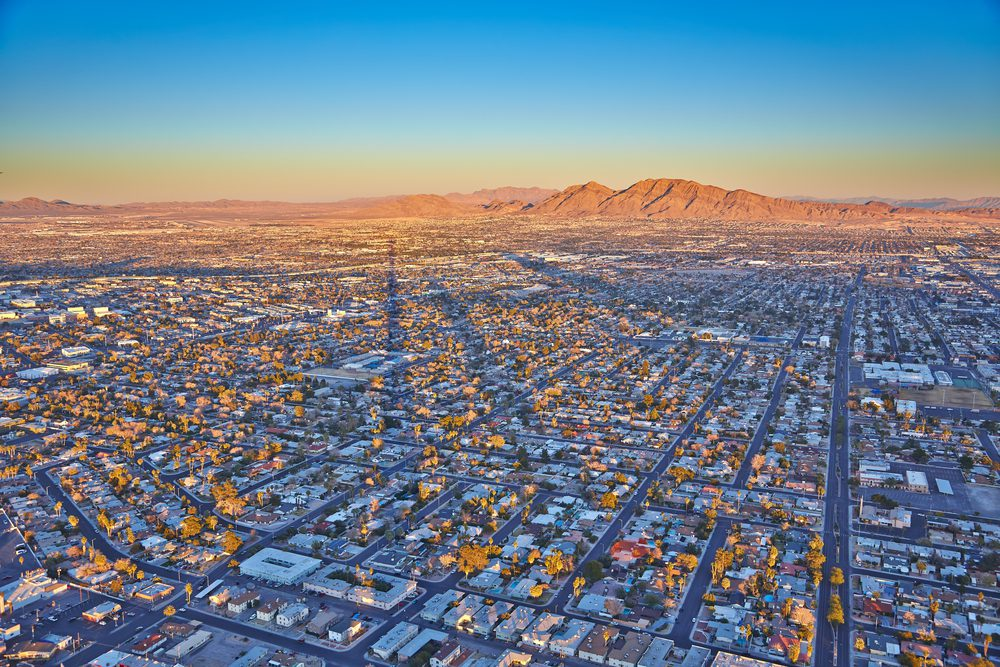 Picture of neighborhoods in Southwest Las Vegas, roof tops to the sunrise over the mountain