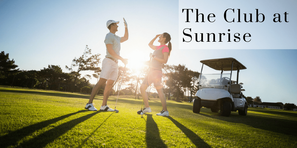 Man and Woman are in golf clothes smiling and giving each other a high five while standing on a golf course in front of a golf cart. Words Read The Club at Sunrise