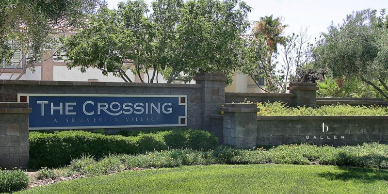 Sign reads The Crossing and is on a wall with green grass and trees at entrance of The Crossing Village in Summerlin