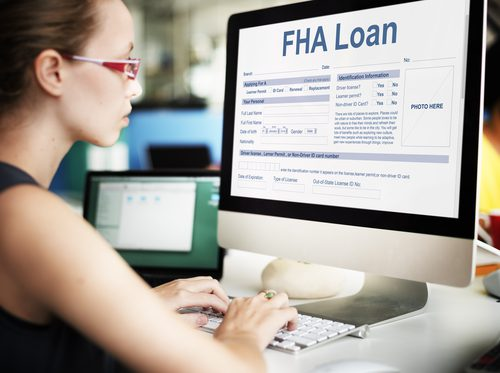 woman sits at large computer and is filling out an application for an FHA loan