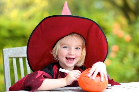 Adorable little girl carving a pumpkin for halloween festivities