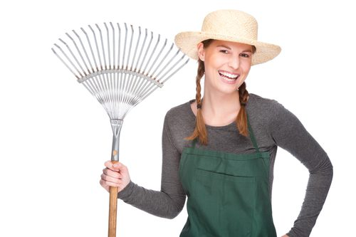 Woman is smiling, wearing braids, hat, green shirt and apron and is holding a rake