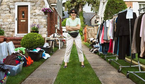 Woman stands in front yard with fanny pack on , arms crossed, hosting a yard sale