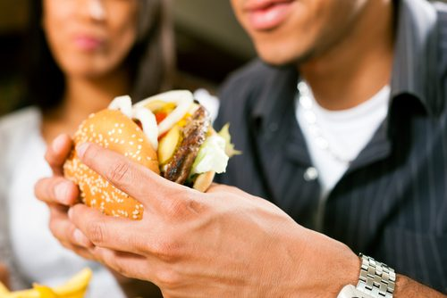 Man and Woman are sitting at a diner eating a well stacked hamburger