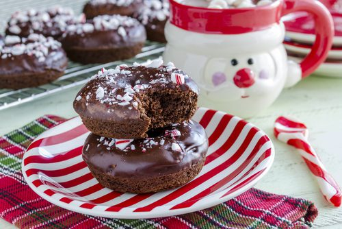 photo of chocolate cookies on candy cane plate next to santa mug with hot cocoa