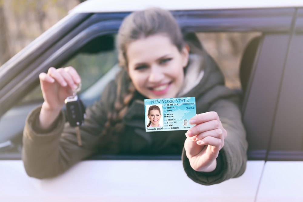Woman is holding a real estate license and smiling out her car window