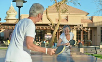 2 grey haired people, a man and a woman, who look to be 55+ are playing ping pong outside with a clubhouse behind them