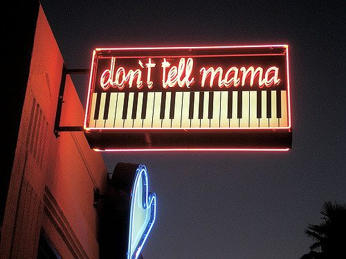 Sign outside of Don't tell mama Karaoke bar is lit up with pieano keys