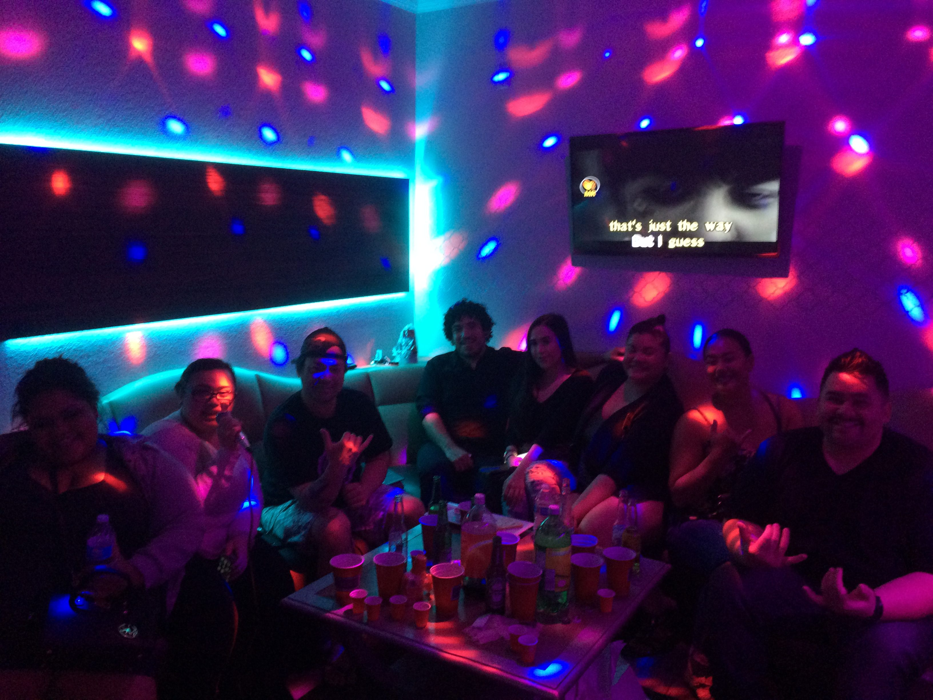 Go Go Karaoke room with group of people having fun at a party, sitting on the couch, karaoke monitor is showing words and someone is holding a microphone