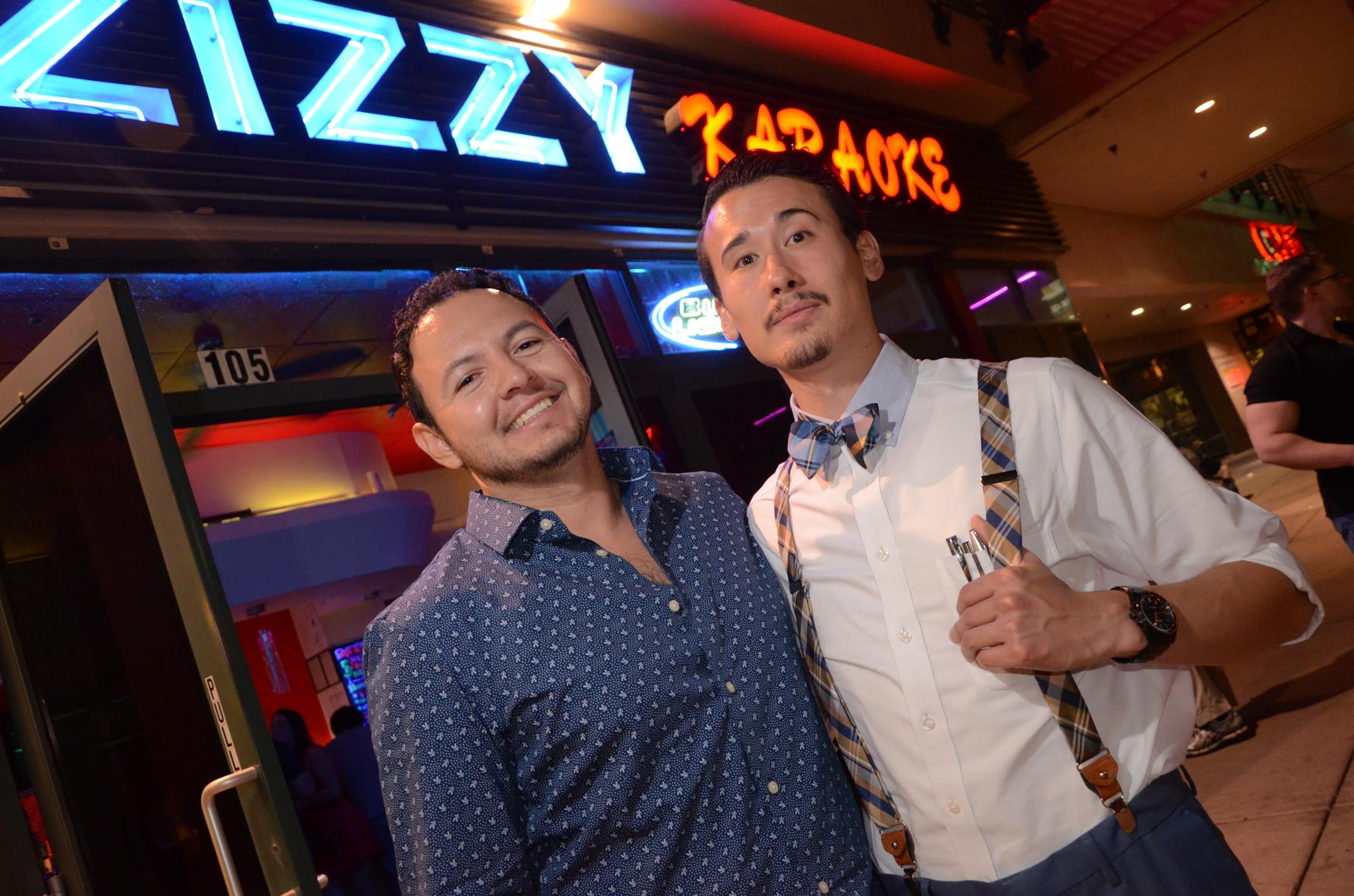 Two men stand outside of Zizzy Karaoke Bar Las Vegas and are smiling, one has thumb up