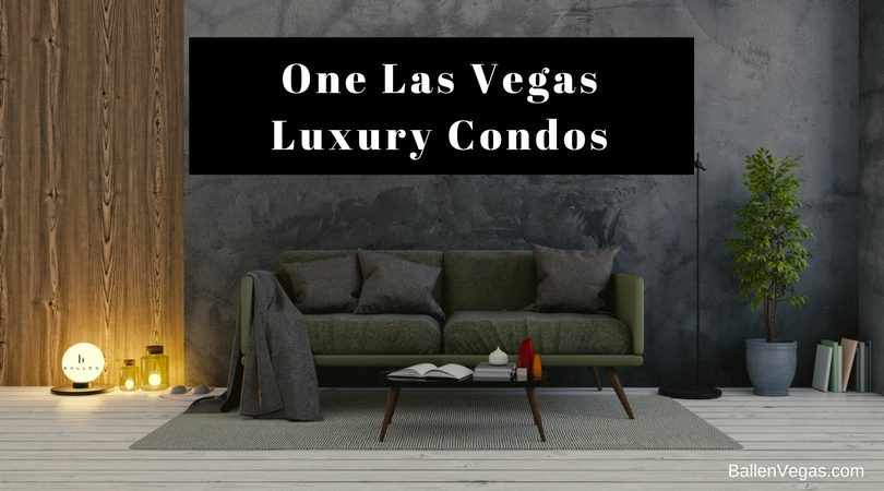 Grey Couch and dark wall with small table are in an open living room. Sign reads one las vegas luxury condos