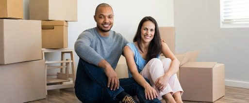 man and woman smiling as they sit among moving boxes