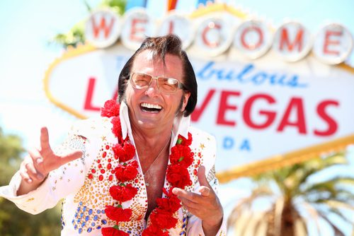 Elvis is standing outside of the Las Vegas sign