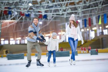 Mom, Dad, Child are skating at what could be the Cosmopolitan Ice skating rink