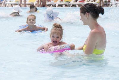 Kids are swimming with tubes and a mom is standing close by holding one of the tubes with a child in it