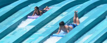 Kids are sliding down head first on a wet and wild water slide