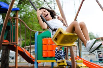 Child is swinging on a yellow swing at the park and smiling or laughing