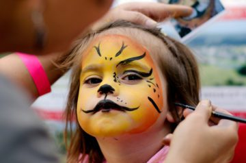 Small child, age 3-5 has her face painted in orange and yelow with whiskers, like they might do at a Springs Preserve Event